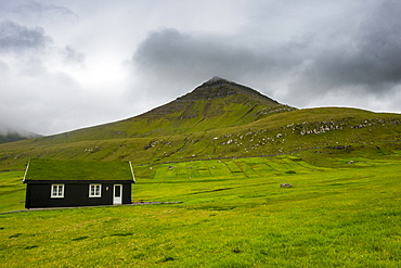 Lonely grass roofed house in Gjogv, Estuyroy, Faroe islands, Denmark