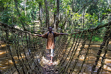 Pygmy walking across a hand made vine bridge in Dzanga-Sangha Park, UNESCO World Heritage Site, Central African Republic, Africa