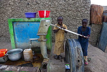 Local kids on a water well, Gaoui, near N'Djamena, Chad, West Africa, Africa