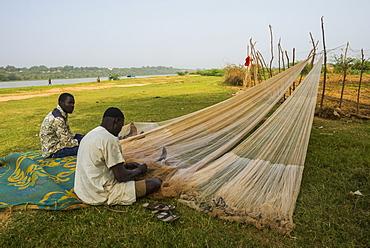 Fishermen repairing their fishing nets on the River Niger, Niamey, Niger, Africa