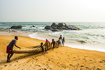 Locals pushing a canoe in the ocean east of Buchanan, Liberia, West Africa, Africa