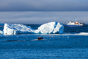 Zodiac cruising back to a cruise ship anchoring behind an iceberg, Brown Bluff, Antarctica, Polar Regions