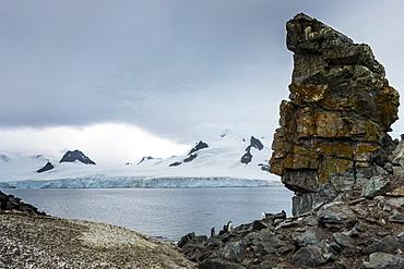 Penguins below dramatic rock formations, Half Moon Bay, South Sheltand Islands, Antarctica, Polar Regions