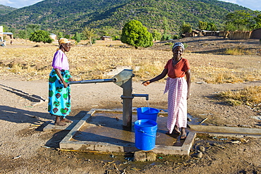 Women pumping water out of a well at Lake Malawi, Cape Maclear, Malawi, Africa