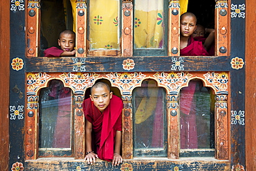 Young novice monks in the window of their quarters, Punakha, Bhutan, Asia