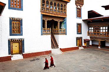 Monks walking through the courtyard of Punakha Dzong, Punakha District, Bhutan, Asia