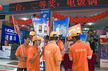 China young men hired to advertise goods outside an electronics shop in kunming, yunnan province