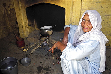 Village life, pakistan. Woman cooking food in a stove in a punjabi village
