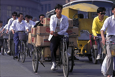 Bicycles, china. Shanghai. Cyclist at a traffic light during rush hour
