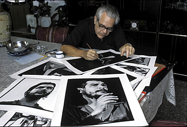 Roberto salas with pictures of 'che' guevara, cuba. The photographer salas looking at his world-famous prints of the guerilla leader, taken in the 1960s