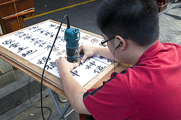China sign-maker with calligraphic skills in the old quarter in guangzhou, guangdong province