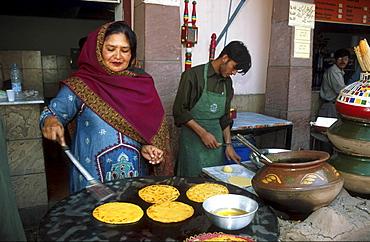 Street kitchen, pakistan. Making pokharas (fried chappatis) at a food stall