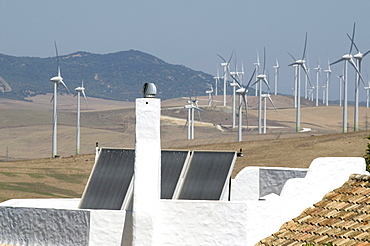 Spain. Wind turbines and houses with solar panels in rural areas in andalucia