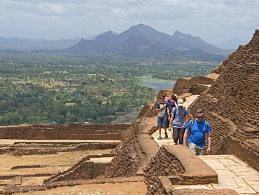 Tourists visit the ancient city of Sigiriya, with carvings on a rock in a mountain fortress, UNESCO World Heritage Site, Sri Lanka, Asia