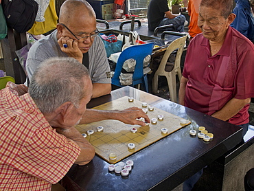 Senior Chinese men playing board game in Chinatown, Singapore, Southeast Asia, Asia