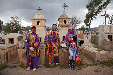 Revellers in costumes and masks at a cemetery in Humahuaca during carnival in Jujuy province in the Andes region of Argentina