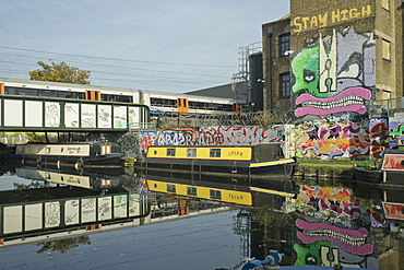 Overground train drives past canal by artists studios and warehouses in Hackney Wick, London, England, United Kingdom, Europe