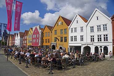 Tourists sit in the sun in outdoor bars and cafes in the old wharf and traditional wooden buildings in the Bryggen quarter of Bergen, UNESCO World Heritage Site, Norway, Scandinavia, Europe