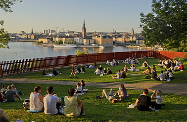 Young people picnic at sunset in the summer in the fashionable Sodermalm neighbourhood and district of Stockholm, Sweden, Scandinavia, Europe