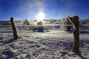 Barb wire fence in winter landscape with hoarfrost, steeming river, brilliant sunshine and blue sky, utah, usa