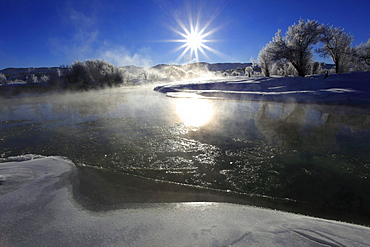 Winter landscape with hoarfrost, steeming river, brilliant sunshine and blue sky, utah, usa