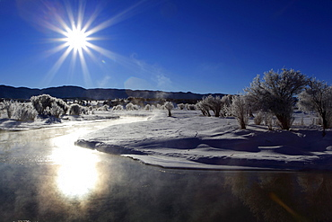 Winter landscape with hoarfrost, steaming river, brilliant sunshine and blue sky, utah, usa