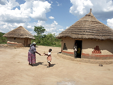 Zambia 7-year-old constance mabo of chikwela village, chongwe, with her grandmother rita, in front of her house