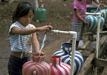 Guatemala girls drawing water standpipe at a resettlement project in the peten