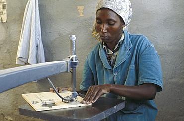 Kenya woman making jigsaw puzzle, nairobi