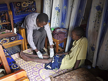 UGANDA The work of Comboni Samaritans, Gulu. Home based care from a volunteer with the Combonis. Ojok Andrew, 36, visiting Lalam Grace, 35, who has AIDS and suffers severe leg pain. He puts on rubber gloves and gives her a massage. PHOTO by Sean Sprague