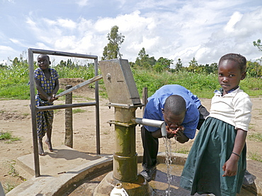 UGANDA Children collecting water from hand-pumped bore well, Gulu. PHOTO by Sean Sprague