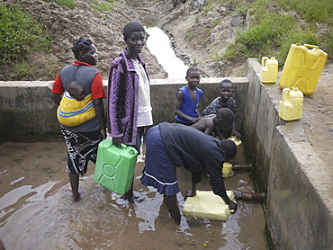 UGANDA Collecting water from hand-pumped well, Gulu. PHOTO by Sean Sprague
