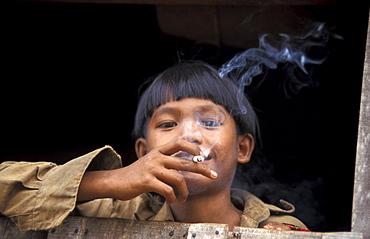 Cambodia boy smoking a cigarette. Malik village. Ratanakiri.