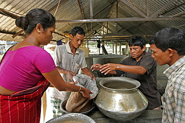 Bangladesh family buying fish fingedrlings for stocking the pond on the farm, at a hatchery in haluaghat, mymensingh region. They are members of the garo tribal minority