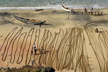 India fishermen arranging their nets on the beach. Varkala beach resort, kerala.