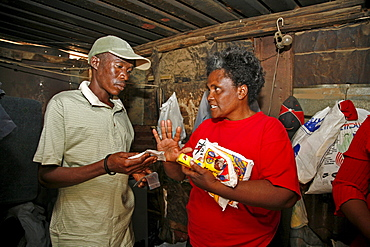 Namibia a voluntary home visitor (right) of catholic aids action visiting a suffering from. is giving a nutrition supplement (anti retro viral) tablets. Rehobeth