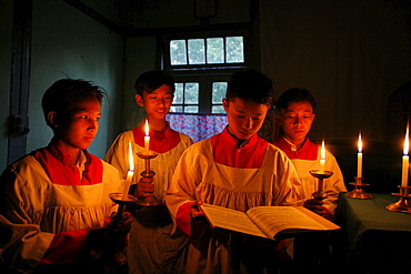 Myanmar boys reciting gospel in candle light at catholic -seminary at myitkyina, a largely kachin community in north burma near chinese border