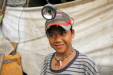 Philippines boy wearing a headlamp. He is getting ready to scavenge on the dump. Shantytown dwelling near garbage tip at bagong silangan, quezon city, manila