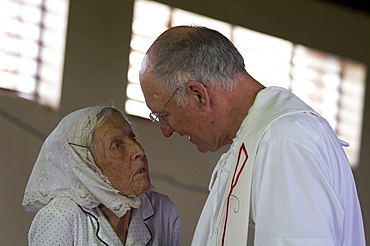 Jamaica. Old woman of german origin talking to american priest during sunday mass in the catholic church at seaford town