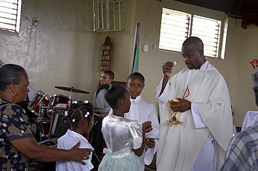 Jamaica. Communion given by father carl clark at sunday mass in the catholic church at seaford town