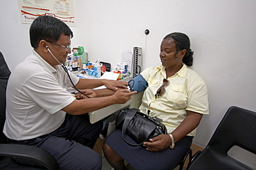 Jamaica. Doctor taking blood pressure in clinic at montego bay