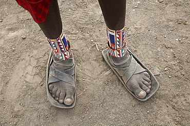 Kenya. Detail of sandals made from car tires and ankle ornaments worn by a masai warrior, masai village within the amboseli national park