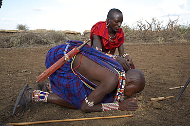 Kenya. Masai men starting a fire the traditional way by rubbing two sticks together and igniting dry elephant dung. Masai village within the amboseli national park