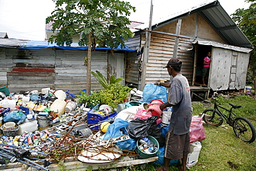 Indonesia mohammed sofyan yusuf, a garbage recycler and crs new house beneficiary, sorting recycables, monikeun, a suburb of banda aceh, aceh, two years after the tsunami