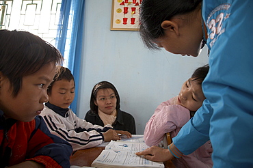 Vietnam yen mo tu commune primary school, ninh binh province. this is one of several schools in this region of northern vietnam where crs in cooperation with the local education authorities has implemented inclusive education practices, whereby children with mental or physical disabilities are integrated into the normal primary schools. crs provides special training for the teachers to help them. the image shows 13-year-old pham thi bich ngoc (in pink jacket) who suffers from cerebral palsy and is intergrated into a class of 11-year-olds. her teacher nguyen thi mund is seen here helping her with an alphabet exercise