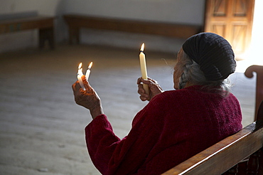 Guatemala woman holding candles in church of chajul, el quiche