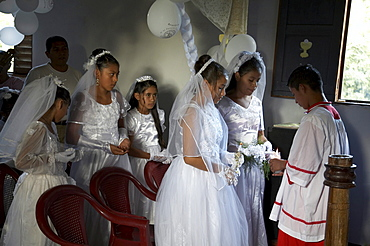 Guatemala catholic first communion and mass at remate, el peten. altar boy lights candles of young girls after the ceremony