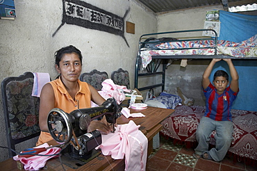El salvador family of teresa de jesus perez, 36, hiv+, left with three sons, one of whom, 8-year-old raphael, is also hiv+. they are supported by contra sida, san salvador. teresa supports herself and family by sewing blouses and dresses at home, shown here with sons raphael, who is hiv+ (on left) and jose, who is not infected