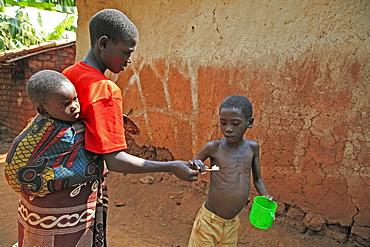 Burundi family of speciose ciza (32) and three children, claude (9), constantin (6) and orave (1). Claude brushing his teeth. Gitera.