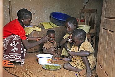 Burundi woman feeding her children, gitera.